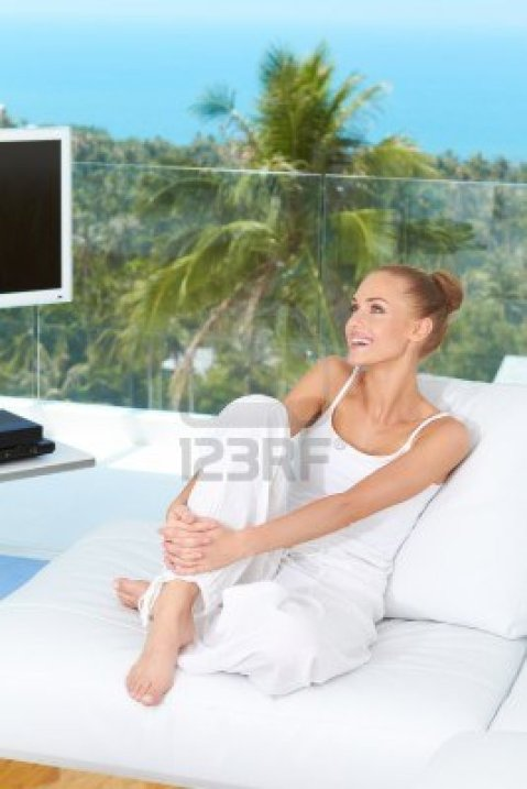 beautiful-happy-woman-sitting-barefoot-on-a-white-sofa-in-her-living-room-with-a-tropical-view-throu